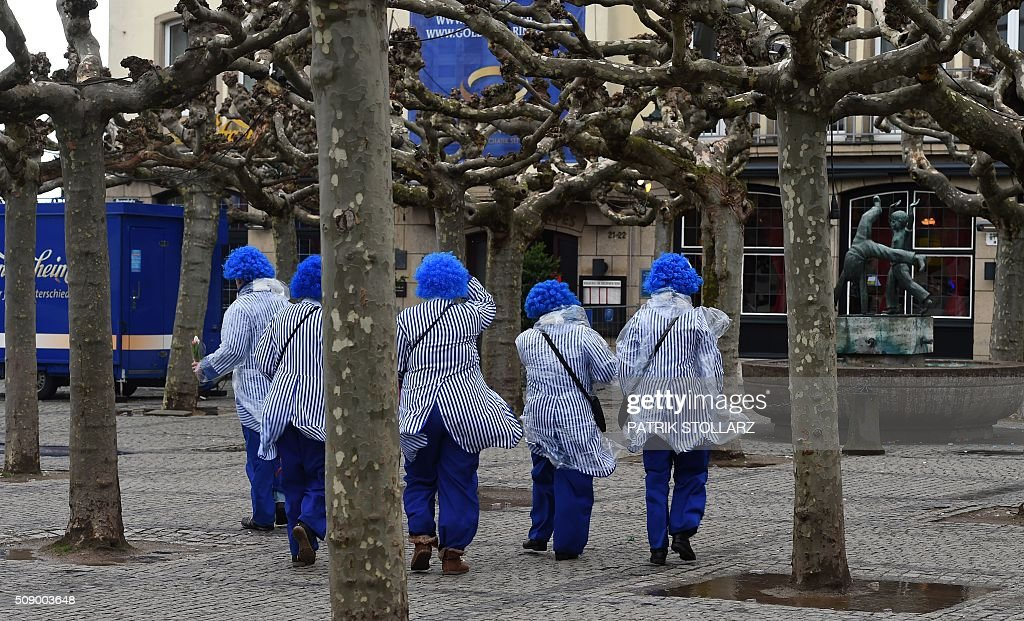 Revellers walk through the streets of Duesseldorf, western Germany, after the Rose Monday (Rosenmontag) street parade has been cancelled due to stormy weather on February 8, 2016. / AFP / PATRIK STOLLARZ