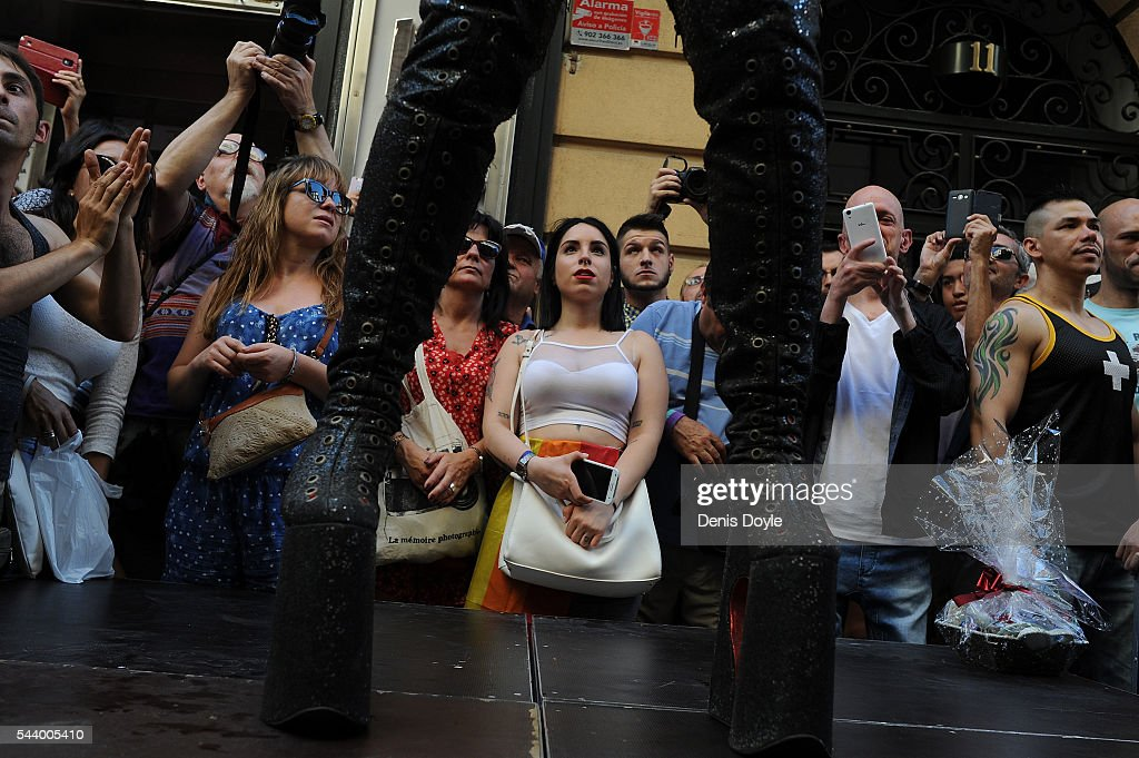 Revellers watch a drag queen dance in platform boots during the 2016 Madrid Gay Pride week on June 30, 2016 in Madrid, Spain. Hundreds of thousands of revellers celebrate the Gay Pride week in Madrid, one of the biggest in Europe.
