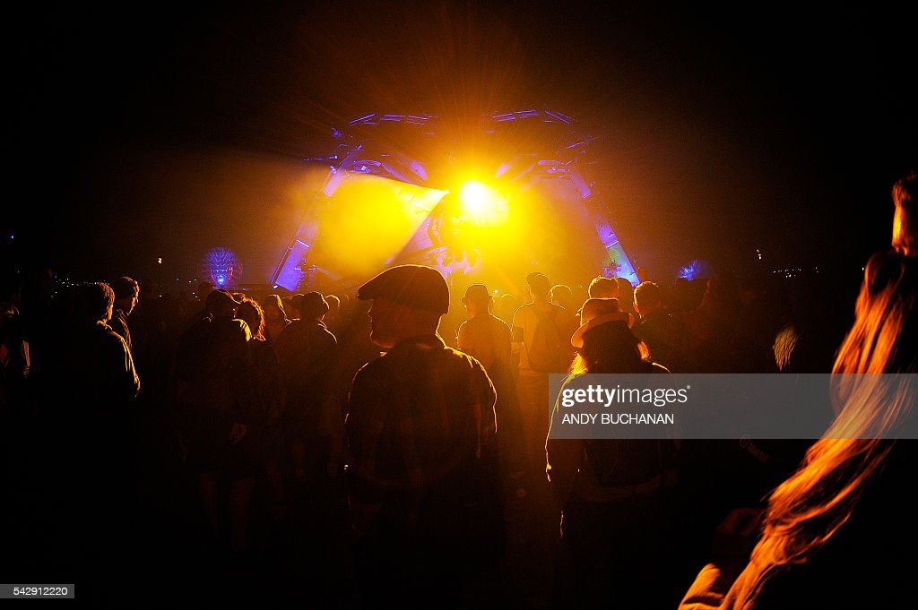 Revellers watch and listen at 'Metamorphosis' in the Arcadia section of the Glastonbury Festival of Music and Performing Arts on Worthy Farm near the village of Pilton in Somerset, south west England on June 25, 2016. / AFP / Andy Buchanan
