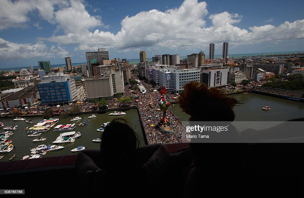 Revellers watch from a hotel rooftop during Carnival celebrations on February 6, 2016 in Recife, Pernambuco state, Brazil. Carnival celebrations continued in the city in spite of concerns over the Zika virus.