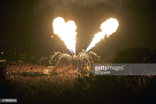 Revellers watch the Arcadia pyrotechnic show at the Glastonbury Festival of Music and Performing Arts on Worthy Farm near the village of Pilton in...