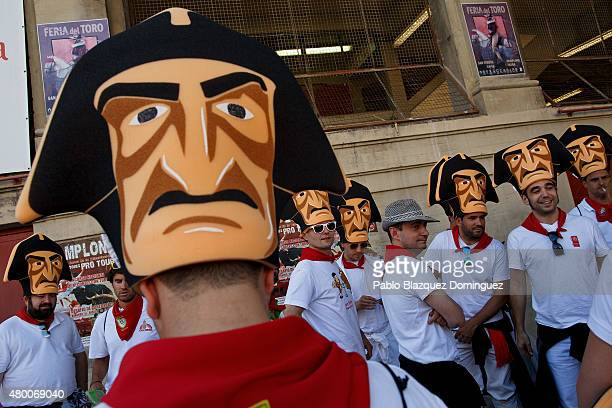 Revellers wearing a hat depicting 'Vinegar face' kiliki meet to enter the bullring before a bull fighting during the fourth day of the San Fermin...