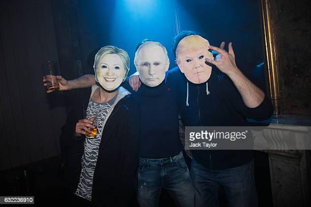 Revellers wearing Hilary Clinton Vladimir Putin and Donald Trump masks pose for a picture at the Old Queens Head during the pub's 'End is Nigh' party...