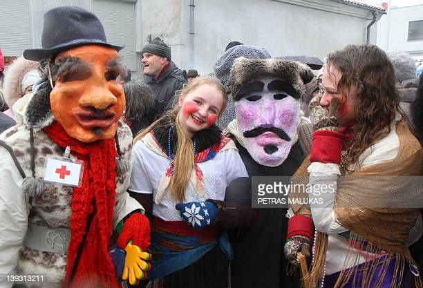Revellers wearing masks and dressed up as Gypsies devils witches horses goats and others parade in the streets of the old town of Klaipeda on...