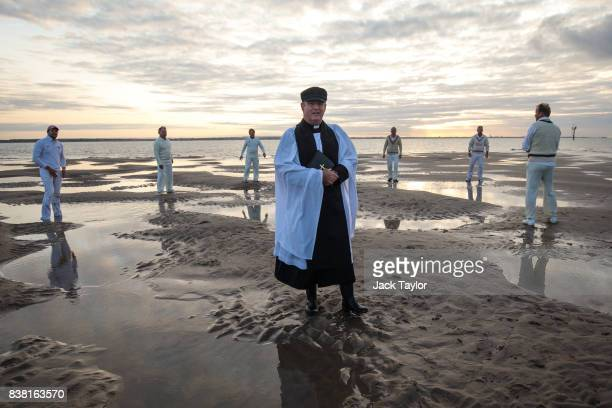 Reverend Andrew Poppe gives a blessing before teams play a cricket match on the Brambles sandbank at low tide on August 24 2017 in Hamble England The...
