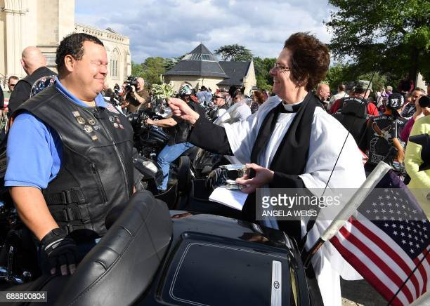 A reverend blesses a Rolling Thunder member during the 'Blessing of the Bikes' at the Washington National Cathedral May 26 2017 in Washington DC /...