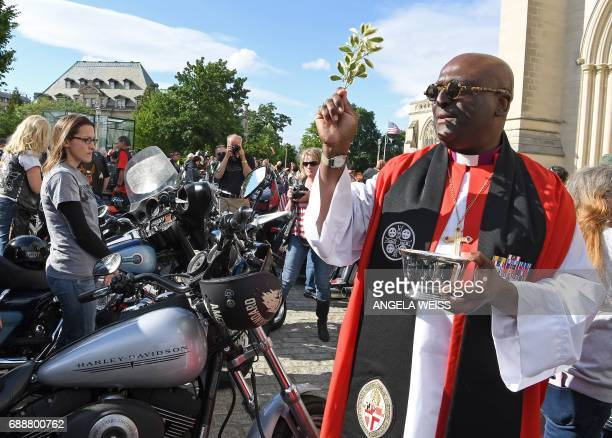 A reverend blesses motorcyclists during the 'Blessing of the Bikes' at the Washington National Cathedral May 26 2017 in Washington DC / AFP PHOTO /...