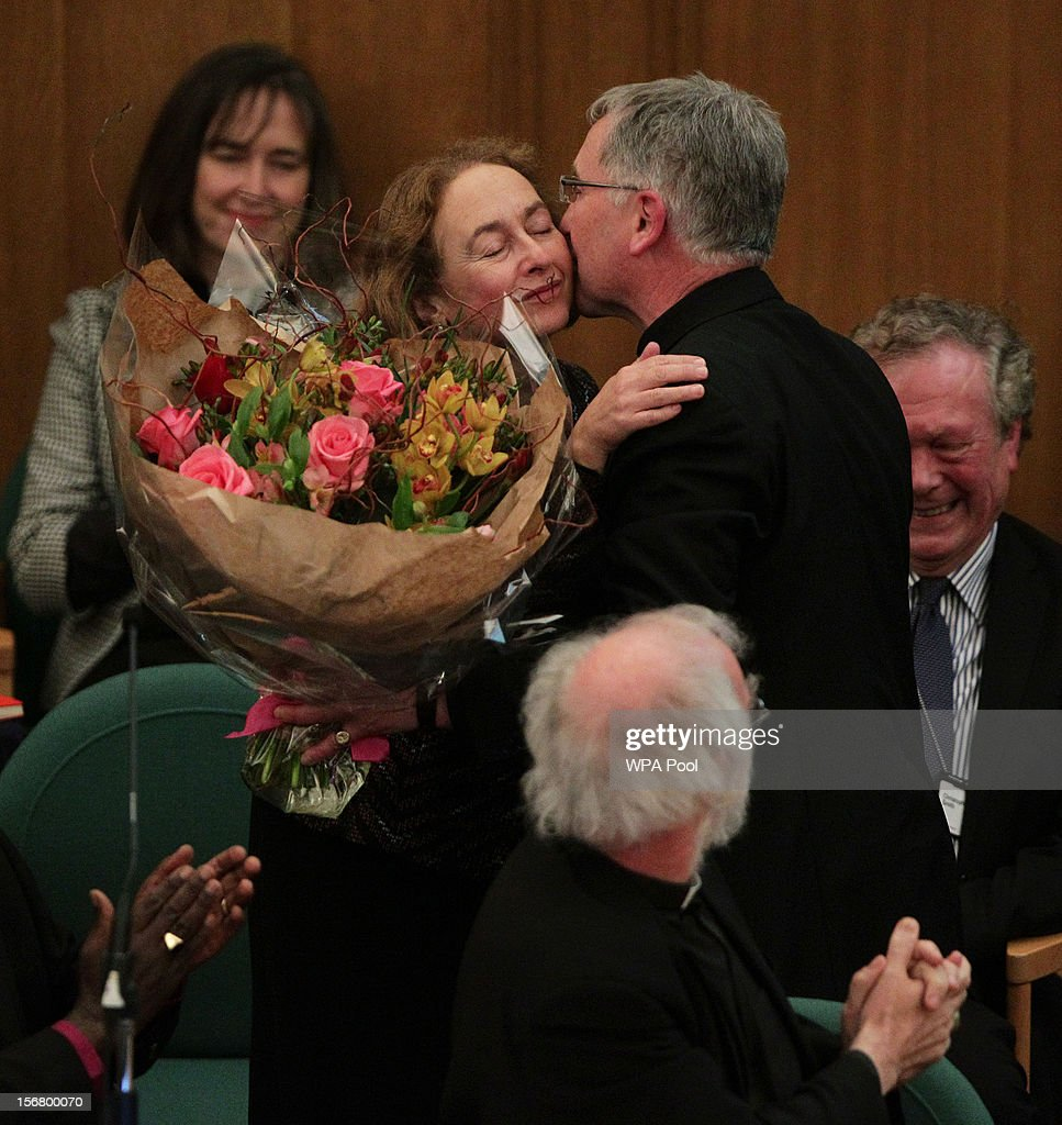 Reverend Canon Glyn Webster presents a bouquet of flowers to Jane Williams, the wife of Dr Rowan Williams (bottom, back to camera), the outgoing Archbishop of Canterbury, after farewell tributes were paid to him at a meeting of the General Synod of the Church of England, at Church House on November 21, 2012 in London, England. The Church of England's governing body, known as the General Synod, yesterday voted to prevent women from becoming bishops. Dr Rowan Williams said that the Church of England had lost a 'measure of credibility', following the General Synod rejected the legislation.