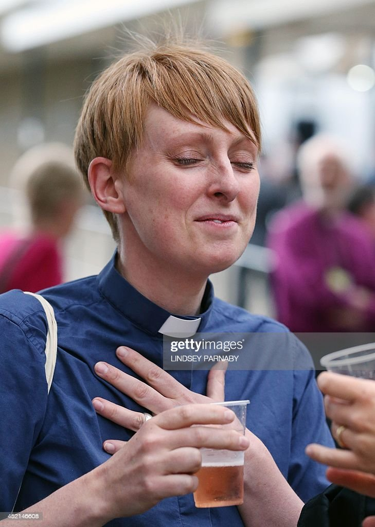 Reverend Claire Turner celebrates with a drink outside the venue after members voted to approve the creation of female bishops at the Church of England General Synod in York, northern England, on July 14, 2014. The Church of England overcame bitter divisions on July 14 to vote in favour of allowing female bishops for the first time in its nearly 500-year history. The decision reverses a previous shock rejection in 2012 and comes after intensive diplomacy by Archbishop of Canterbury, Justin Welby.