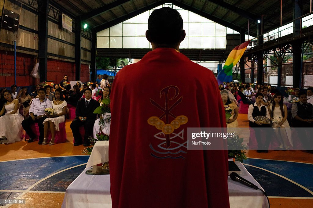 "Reverend Cresencio ""Ceejay"" Agbayani delivers a sermon during a mass wedding ceremony at Barangay Sangandaan in Quezon City on Sunday, 26 June 2016. The LGBT Christian Church, a small Christian ecumenical group, performed its own ""wedding rites"" for eight couples at a basketball court on Sunday, although same-sex unions are not legally recognized and rejected by the dominant Roman Catholic church in the country."