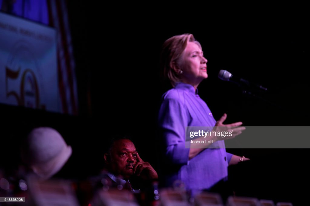 Reverend Jesse Jackson, left, listens as Democratic presidential candidate Hillary Clinton deliveres the keynote speech during the Rainbow PUSH Coalition's International Women's Luncheon June 27, 2016 in Chicago Illinois. Clinton addressed gun violence across the country and referred to the Orlando, Florida Pulse nightclub shooting and the uptick in gun crime across Chicago.