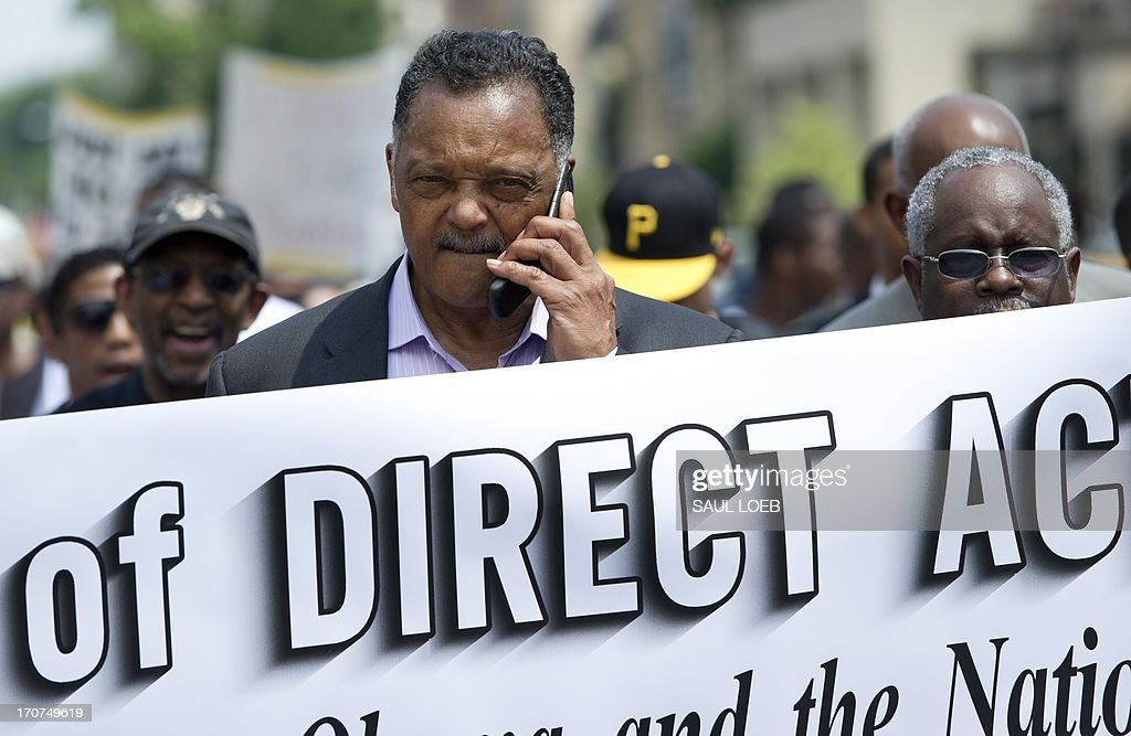 Reverend Jesse Jackson (C), talks on his cellphone during a protest march calling on US President Barack Obama to end the so-called 'War on Drugs,' which they say leads to mass incarceration of African Americans, as well as wanting additional investment in jobs and economic development in urban inner-city neighborhoods, during a 'Day of Direct Action' march through the streets of Washington on June 17, 2013, enroute to Lafayette Park adjacent to the White House. AFP PHOTO / Saul LOEB
