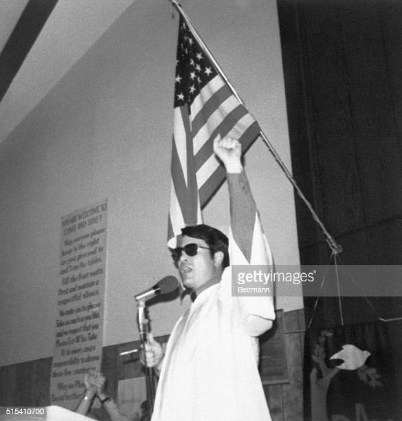 Reverend Jim Jones raises his fist in a black power salute while preaching at an unknown location This is one of the photographs from a photo album...