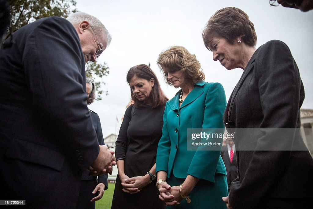 Reverend Jim Wallis prays with Sen Kelly Ayotte Sen Lisa Murkowski and Sen Susan Collins in front of the Capitol Building on the morning of October...