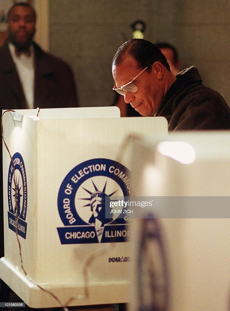 Reverend Louis Farrakhan, leader of the Nation of Islam, votes in Chicago, IL 03 November as members of his ever-present entourage look on from a distance. AFP Photo/John ZICH