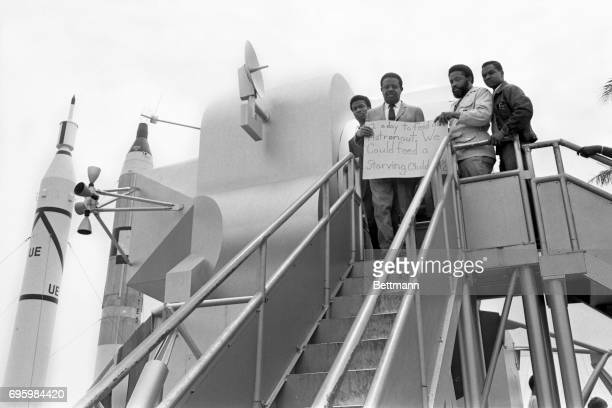 Reverend Ralph Abernathy flanked by associate Hosea Williams stand on steps of a mockup of the lunar module displaying a protest sign while...
