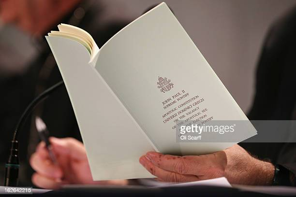 Reverend Thomas Rosica reads a book by the late Pope John Paul II on the 'Apostolic Constitution' during a press conference in the Holy See Press...