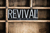 """The word """"REVIVAL"""" written in vintage metal letterpress type in a wooden drawer with dividers."""