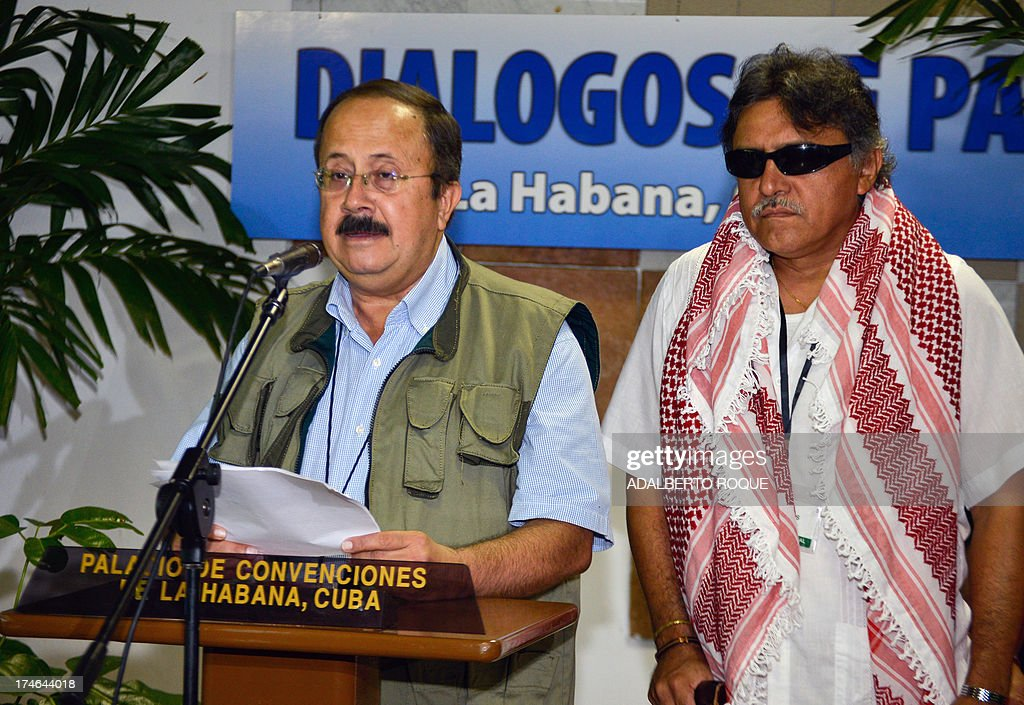 Revolutionary Armed Forces of Colombia (FARC) commander Andres Paris (L) reads a document next to commander Jesus Santrich at the Convention Palace, in Havana on July 28, 2013, before the 12th round of peace talks with the Colombian government's delegation. Colombia will not agree to a ceasefire with FARC rebels until a five-point agenda had been agreed, the Colombian President Juan Manuel Santos stressed Saturday ahead of a resumption of peace talks.