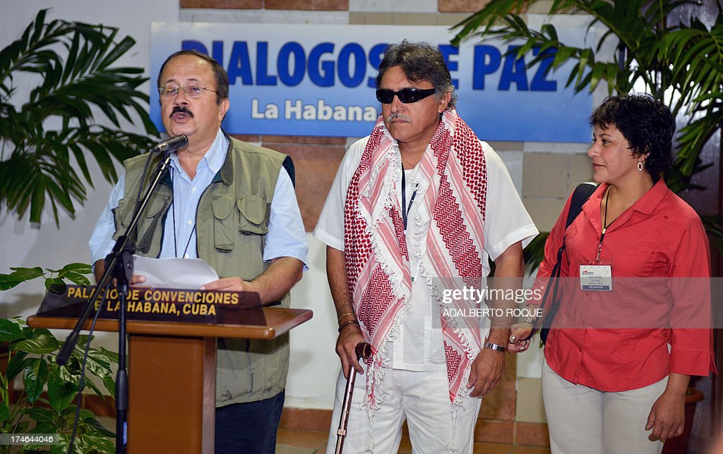 Revolutionary Armed Forces of Colombia (FARC) commander Andres Paris reads a document next to FARC commander Jesus Santrich and fighter Maritza Garcia at the Convention Palace, in Havana on July 28, 2013, before the 12th round of peace talks with the Colombian government's delegation. Colombia will not agree to a ceasefire with FARC rebels until a five-point agenda had been agreed, the Colombian President Juan Manuel Santos stressed Saturday ahead of a resumption of peace talks. AFP PHOTO/ADALBERTO ROQUE
