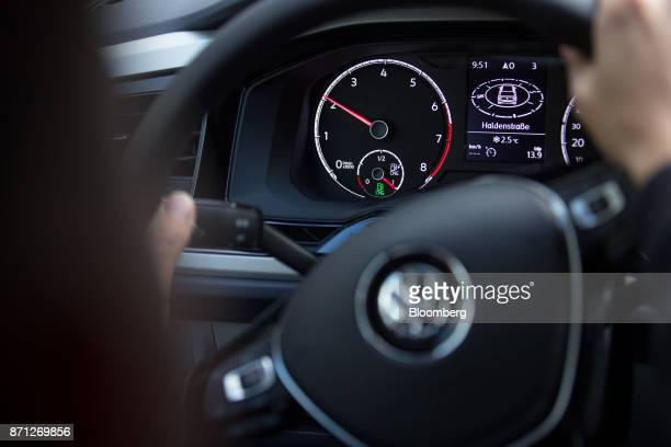 A revolutions per minute counter and fuel gauge sit on the dashboard as an employee drives a Volkswagen AG Polo TGI compressed natural gas fueled...