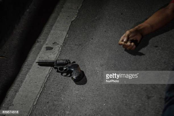A revolver lies next to the body of a man who was killed by police during a police operation in Manila Philippines August 17 2017 Amidst the drug...