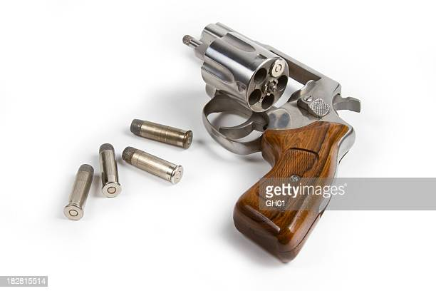 Revolver with bullets on white background