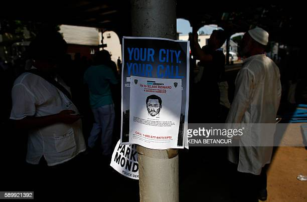 A reward poster for the suspected perpetrator hangs on street post as people as Community members march in protest in the streets after funeral...