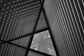 Reworked close-up photo of sloped walls / pitched roof / ceiling. Realistic though unreal industrial interior. Abstract black and white modern architecture background image.