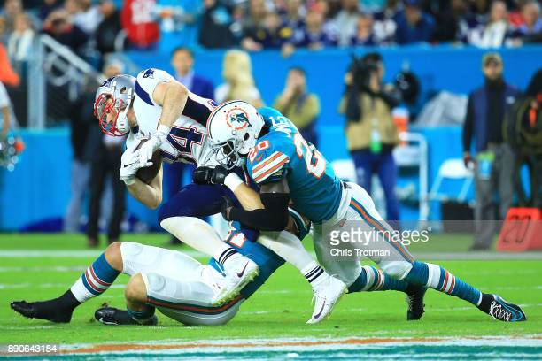 Rex Burkhead of the New England Patriots tries to avoid the tackle from Reshad Jones of the Miami Dolphins during the second quarter at Hard Rock...