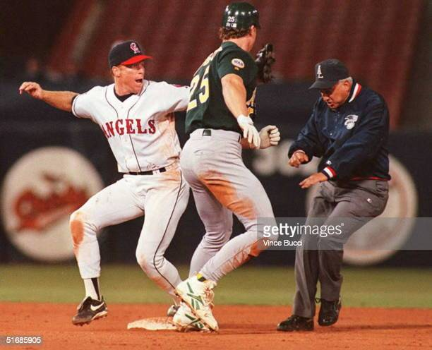 Rex Hudler of the California Angels reacts to umpire Rich Garcia's safe call after Mark McGwire of the Oakland Athletics avoids the tag at second...