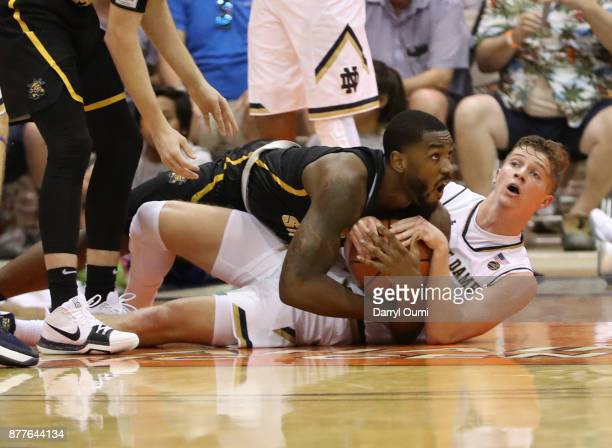 Rex Pflueger of the Notre Dame Fighting Irish and Shaquille Morris of the Wichita State Shockers go to the floor chasing after a loose ball to force...