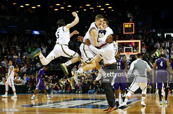 Rex Pflueger of the Notre Dame Fighting Irish and teammates celebrate their 76 to 75 win over the Stephen F Austin Lumberjacks during the second...