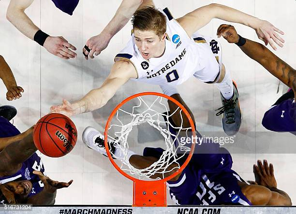 Rex Pflueger of the Notre Dame Fighting Irish tips in a shot to defeat the Stephen F Austin Lumberjacks 76 to 75 in the second half during the second...