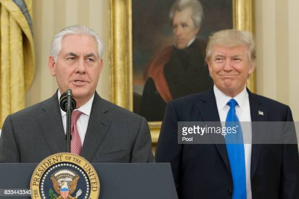 Rex Tillerson delivers remarks after being sworn in as 69th secretary of state as President Donald Trump looks on beneath a painting of populist...