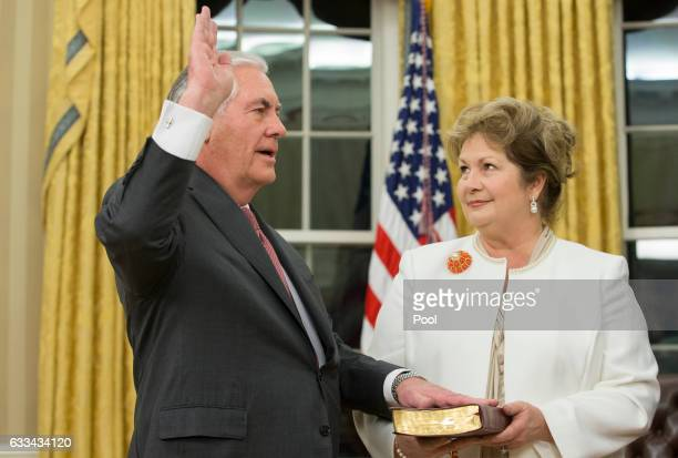 Rex Tillerson with his wife Renda St Clair holding the Bible is sworn in as the 69th secretary of state in the Oval Office of the White House on...