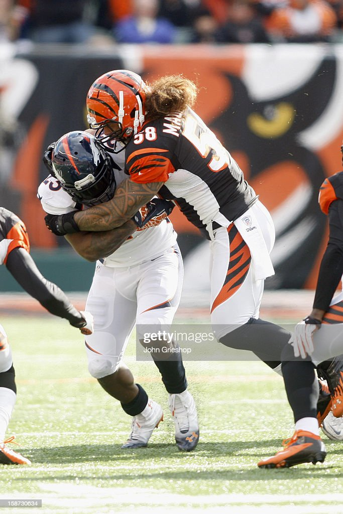 Rey Maualuga #58 of the Cincinnati Bengals tackles Willis McGahee #23 of the Denver Broncos during their game at Paul Brown Stadium on November 4, 2012 in Cincinnati, Ohio.