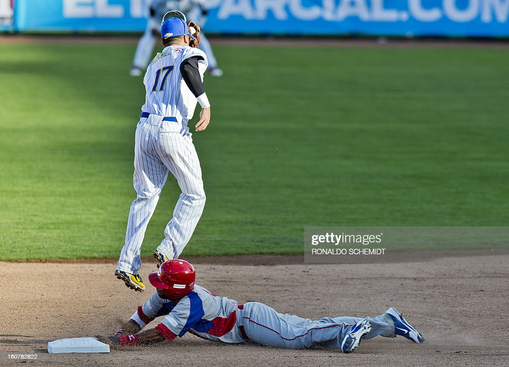 Rey Navarro (bottom) of Criollos de Caguas of Puerto Rico, slides safe in second base in a match against Magallanes of Venezuela, during the 2013 Caribbean baseball series, on February 5, 2013, in Hermosillo, Sonora State, in the northern of Mexico. AFP PHOTO/Ronaldo Schemidt