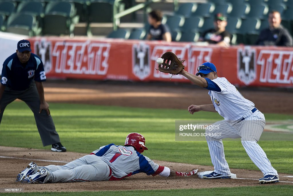 Rey Navarro (L) of Criollos de Caguas of Puerto Rico, slides safe in first base in a match against Magallanes of Venezuela, during the 2013 Caribbean baseball series, on February 5, 2013, in Hermosillo, Sonora State, in the northern of Mexico. AFP PHOTO/Ronaldo Schemidt