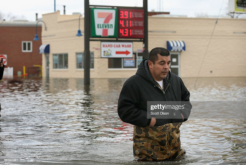 Reyes Garcia wades through flooded downtown street April 19, 2013 in Des Plaines, Illinois. The suburban Chicago town is battling rising floodwater from the Des Plaines River which is expected to crest at a record 11 feet later today. Record-setting rains and rising rivers have caused wide-spread flooding in many Illinois communities.