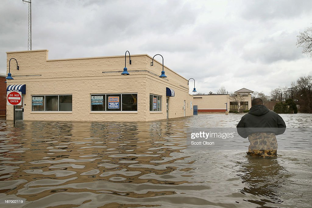 Reyes Garcia wades through floodwater to inspect flood damage to a building April 19, 2013 in Des Plaines, Illinois. The suburban Chicago town is battling rising floodwater from the Des Plaines River which is expected to crest at a record 11 feet later today. Record-setting rains and rising rivers have caused wide-spread flooding in many Illinois communities.