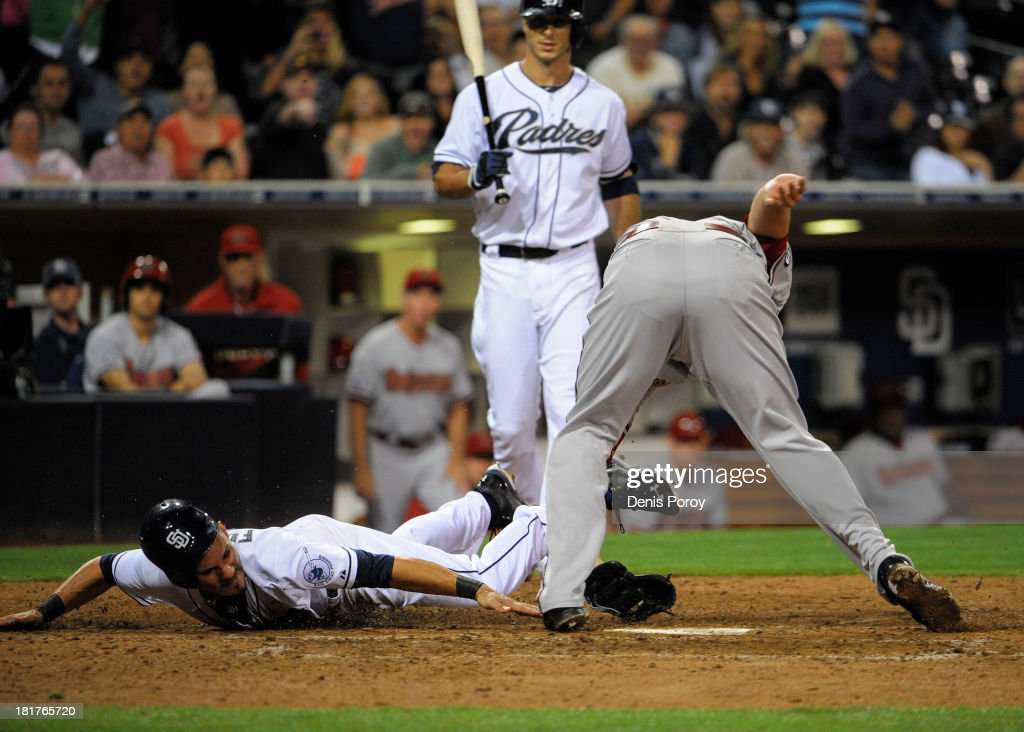 Reymond Fuentes #27 of the San Diego Padres scores past the tag of David Hernandez #30 of the Arizona Diamondbacks on a passed ball during the eighth inning of a baseball game at Petco Park on September 24, 2013 in San Diego, California.