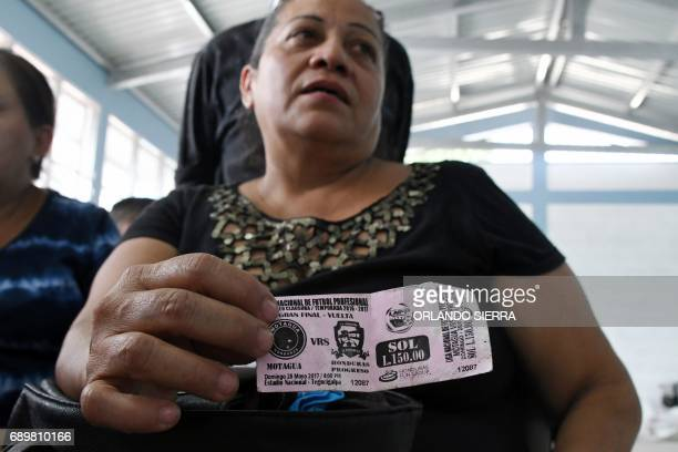 Reyna Funez holds the ticket which her late husband Jose Vidal Zuniga Espinoza was supposed to use to get to the Stadium during the Honduras'...