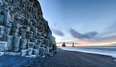 Wide view of Reynisdrangar rock formations on Reynisfjara Beach at sunrise, Halsanefhellir, Iceland.