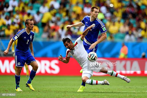 Reza Ghoochannejhad of Iran and Toni Sunjic of Bosnia and Herzegovina compete for the ball during the 2014 FIFA World Cup Brazil Group F match...
