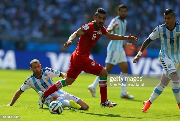 Reza Ghoochannejhad of Iran in action Javier Mascherano of Argentina during the 2014 FIFA World Cup Brazil Group F match between Argentina and Iran...