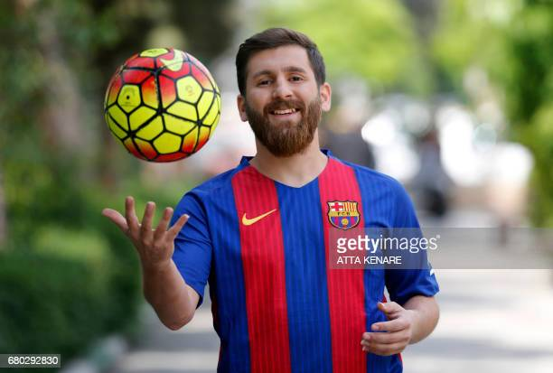 TOPSHOT Reza Parastesh a doppelganger of Barcelona and Argentina's footballer Lionel Messi poses for a picture in a street in Tehran on May 8 2017 /...