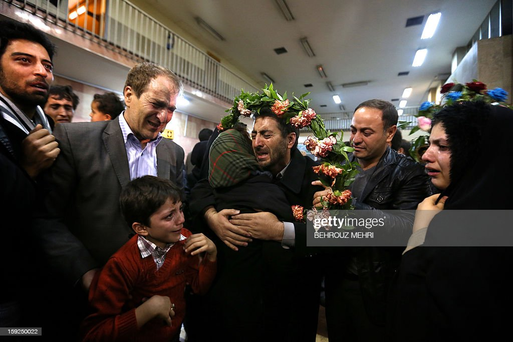Reza Sohrabi (C), an Iranian man who has been held hostage, alongside 48 other Iranians, by Syrian rebels since early August 2012, hugs a relative after arriving at Tehran's Mehrabad airport on January 10, 2013. The rebels agreed to swap the 48 Iranians, described by the Islamic republic as pilgrims but by the rebels and Washington as members of Iran's elite Revolutionary Guards, for more than 2,000 detainees held by the Syrian regime. AFP PHOTO / BEHROUZ MEHRI