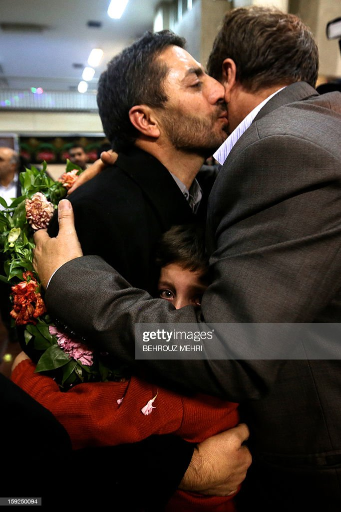 Reza Sohrabi (L), an Iranian man who has been held hostage, alongside 48 other Iranians, by Syrian rebels since early August 2012, hugs his son as he kisses a relative after arriving at Tehran's Mehrabad airport on January 10, 2013. The rebels agreed to swap the 48 Iranians, described by the Islamic republic as pilgrims but by the rebels and Washington as members of Iran's elite Revolutionary Guards, for more than 2,000 detainees held by the Syrian regime. AFP PHOTO / BEHROUZ MEHRI