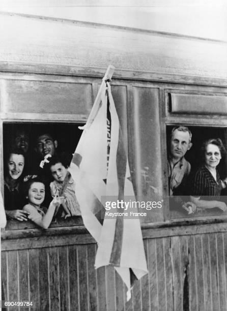 Réfugiés de tout âge brandissant leur drapeau sont tout sourire dans le train qui les ramènent sur leur 'Terre promise' après un long voyage à...